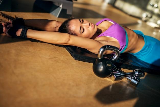 ケトラーボールとジムの頭の近くの2つの小さなダンベルの黒いマットで休んで魅力的な若いフィットネス女の子。