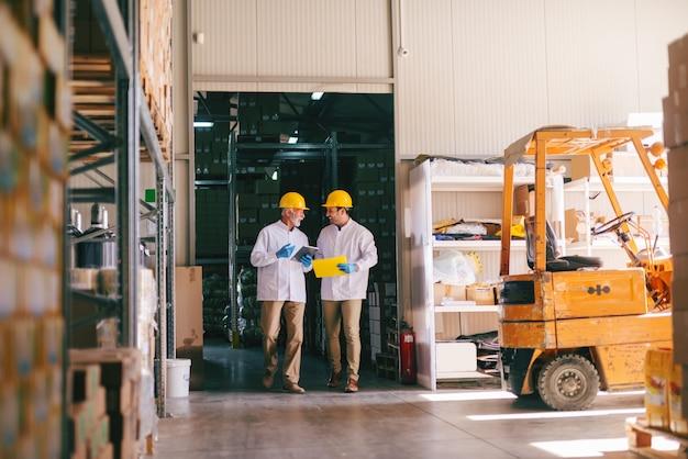 倉庫を歩いて頭にヘルメットを持つ2人の労働者。棚や箱の周り。