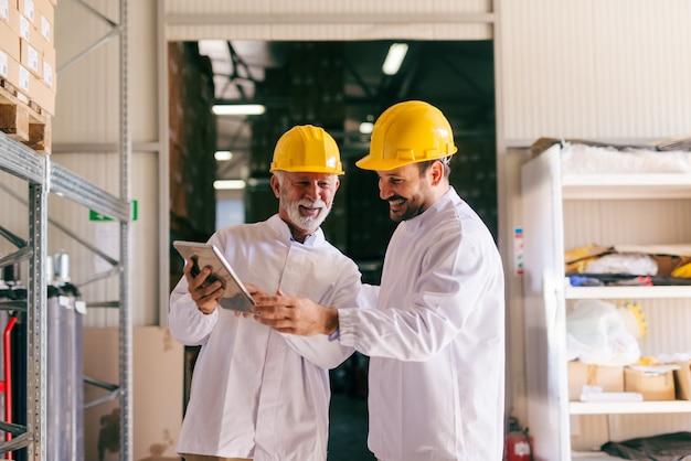 倉庫に立っている間タブレットを見て2人の男性の同僚。