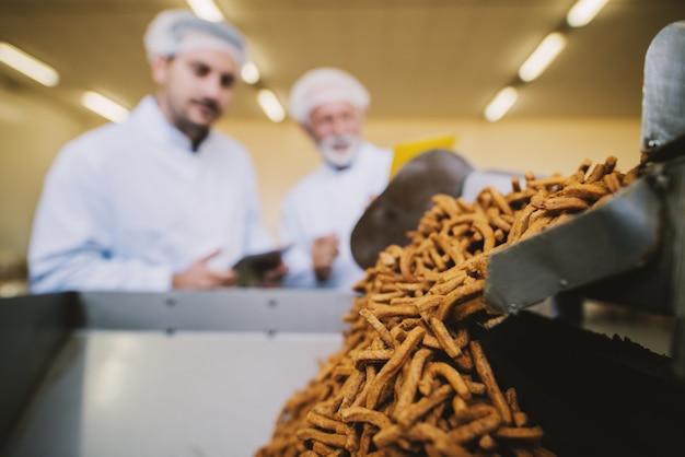 食品工場の生産ラインで塩味のスナックを閉めてください。バックグラウンドで滅菌の服の2つのビジネスの男性の画像がぼやけ。