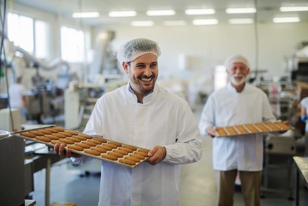 食品工場で新鮮なクッキーがいっぱい入ったトレイを運ぶ無菌の服を着た2人の幸せな笑顔の男性従業員の写真。お互いに助け合って、元気そうに見えます。