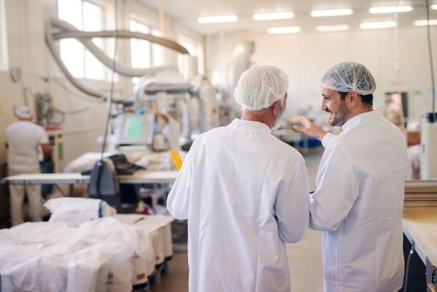 食品工場で話している2人の男性。