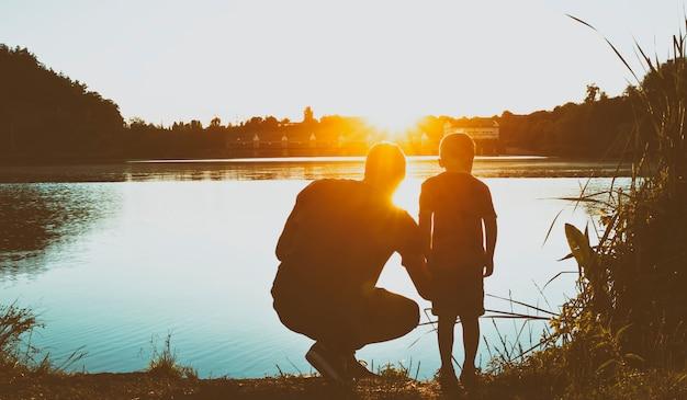 2人の兄弟は日没で湖の岸に立っています。