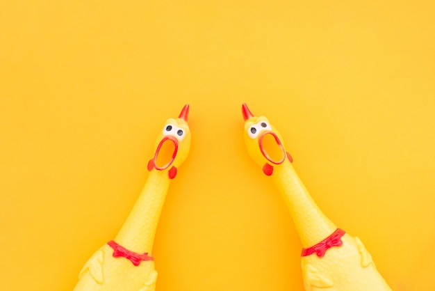 2つの叫んでいる鶏のおもちゃが黄色の背景に分離されており、口を開けてカメラに向かって叫んでいます。