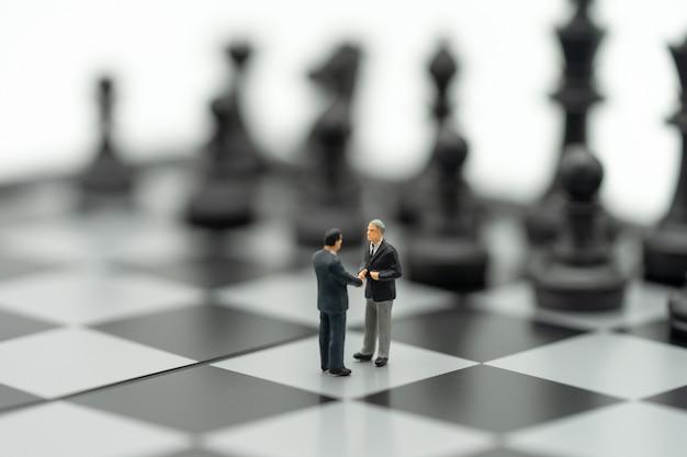 ミニチュア2人ビジネスマンチェスの駒でチェス盤に手を振る