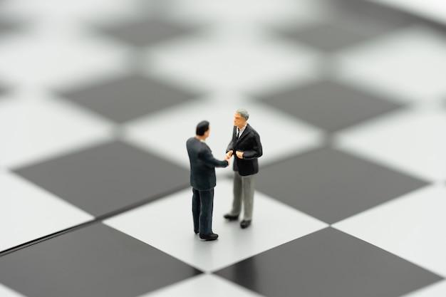 ミニチュア2人のビジネスマンチェスの駒でチェス盤に手を振る