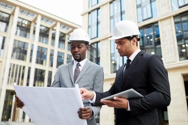 屋外に立っている青写真を扱うヘルメットを身に着けている2人の建築家の上半身ショット