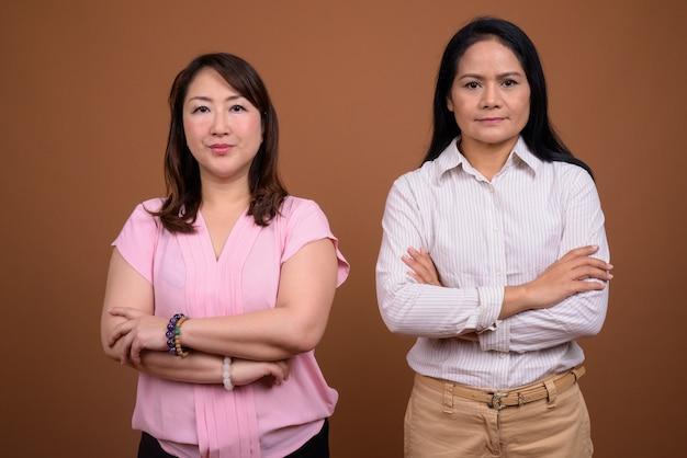 茶色の壁に対して一緒に2人の成熟したアジアのビジネスウーマン