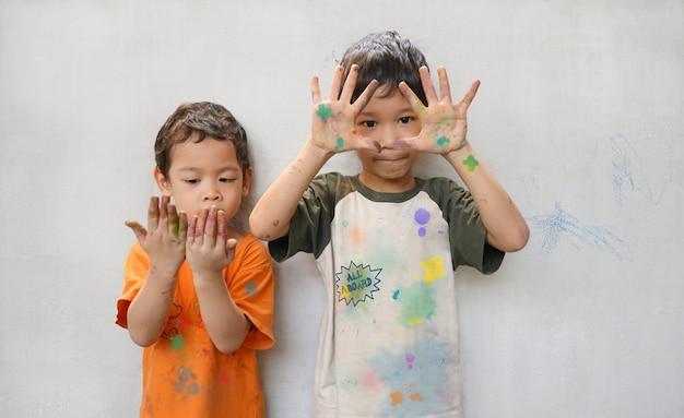 かわいい小さな2つのアジアの男の子の兄弟は、活動創造性の時間で楽しい色を再生します