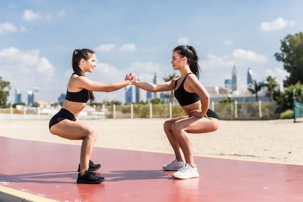 チームワークの強さ。日の出と海を背景にスクワットをしているビーチで2人の若い魅力的な女性アスリートが運動します。