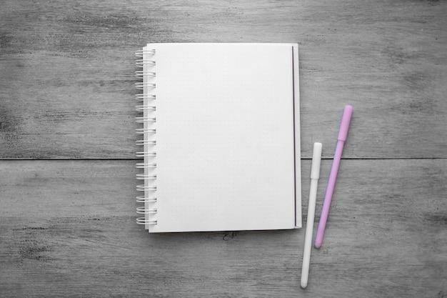 白いノートと白い木製のテーブルに2つのペン