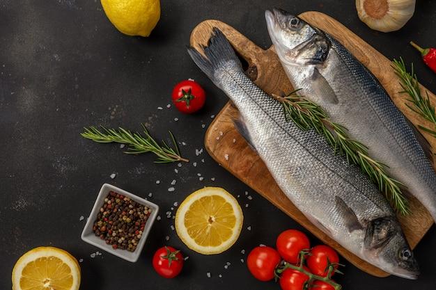 ローズマリーと黒いテーブルで野菜と2つの新鮮なシーバス魚。シーフードのコンセプトです。