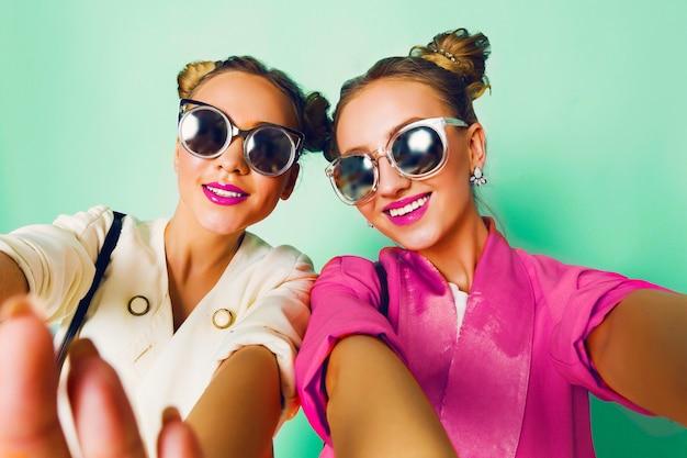 楽しいスタイリッシュなカジュアルな春の服装の2人の若い女性のファッションスタジオ画像は、舌を示しています。明るくトレンディなパステルカラー、バンズのあるスタイリッシュなヘアスタイル、クールなサングラス。友達の肖像画。