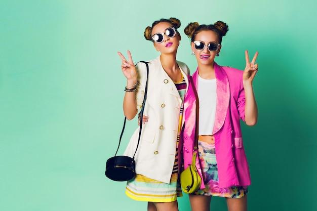 Фасонируйте изображение студии 2 молодых женщин в стильном вскользь весеннем оборудовании имея потеху, покажите язык. яркие модные цвета, стильная прическа с булочками, классные солнцезащитные очки. портрет друзей.