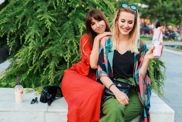 2つの笑顔の女性の話と日当たりの良い近代的な都市で一緒に時間を過ごす