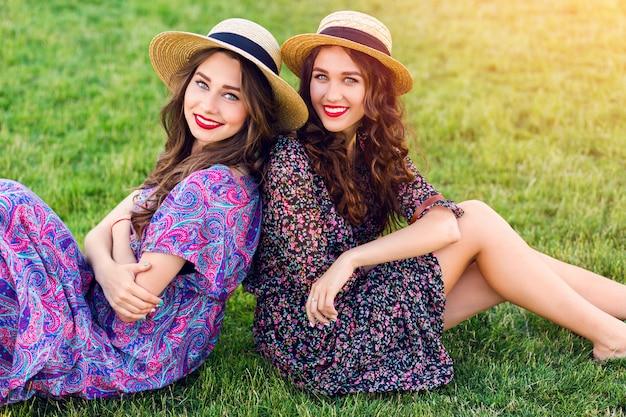 緑の牧草地に座っている2人の陽気な双子が一緒に時間を楽しんでいます。