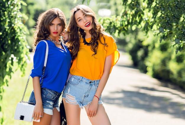 夏の公園を歩いている2人の美しい女の子が話を終了します。スタイリッシュなシャツとジーンズのショートパンツを着て、休日を楽しんでいる友人。