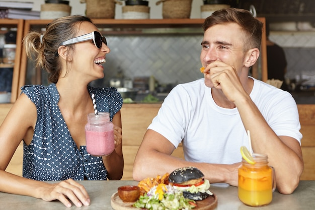 一緒に楽しんで、コーヒーショップでランチを食べながら笑っている2人の親友。彼女のハンサムなボーイフレンドとの活発な会話を楽しんでいるピンクのスムージーの魅力的な女性保持ガラス