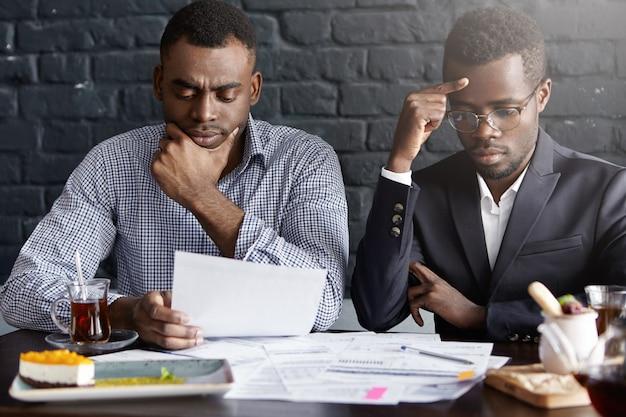 2人の心配している真面目なアフリカ系アメリカ人のビジネスマンが書類を読み、見た目が集中している財務報告について話し合っている