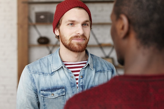 嬉しいです。ハンサムなファッショナブルな若い白人男性の屋内ショット。 2人の友人が会話を楽しみ、ニュースについて話し合う