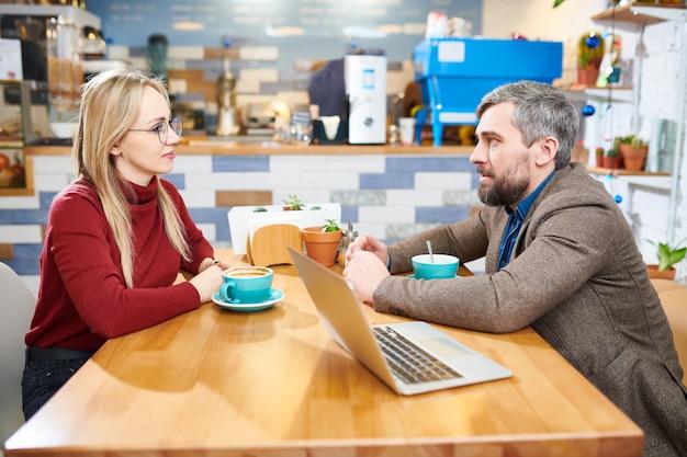 作業点の議論中に向かい合ったカフェのテーブルでスマートカジュアルに座っている自信の若い2人の従業員