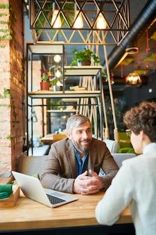 正装で2人の同僚がテーブルの前に座ってブレーンストーミングを行い、会議でアイデアについて話し合っている