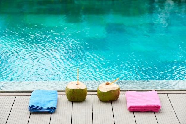 プールの近くの2つのココナッツドリンク