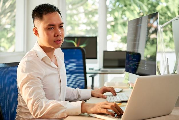 彼の仕事で2台のコンピューターを使用しているマネージャー