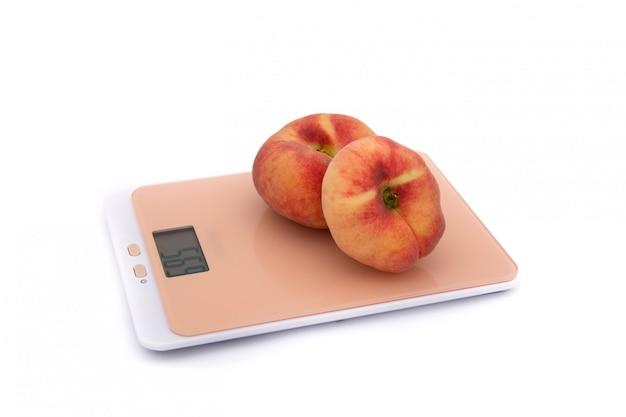 白のキッチンスケールの2つの平らな桃