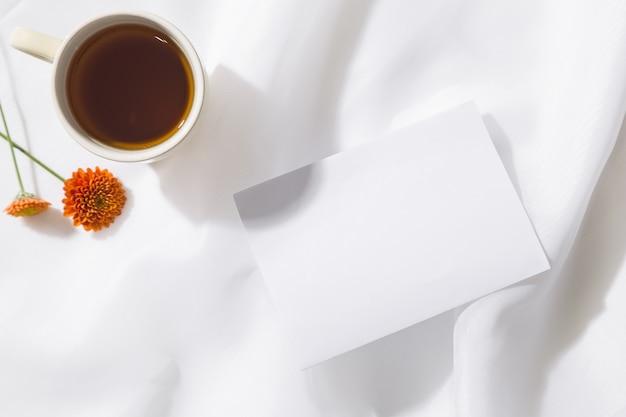 茶マグカップ、2つのオレンジ色の花、テキスト用のスペースと白い紙の上のボイル生地背景の平面図です。横型