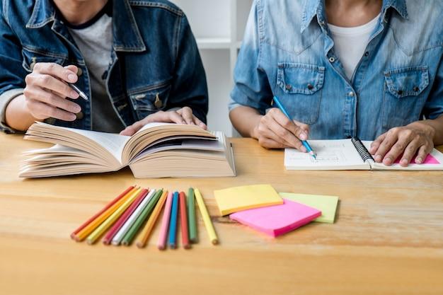 教育、教育、学習、技術、そして人々の概念。 2人の高校生またはクラスメートと友達が教室で宿題を学ぶのを助け、友達と家庭教師の本