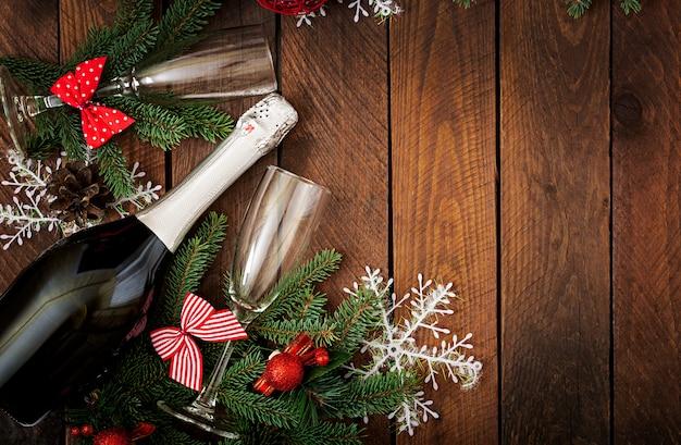 シャンパンのボトルとクリスマスデコレーション、新年あけましておめでとうございますと2つのメガネ