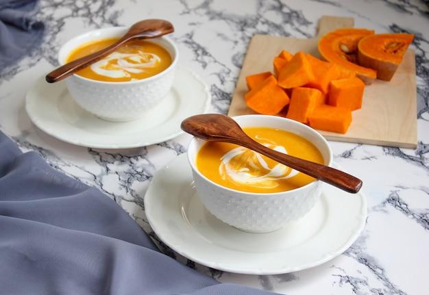灰色の生地とバターナットスカッシュのスライスと白のカボチャスープの2つのボウル