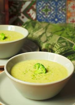 大理石のスプーンで皿の上の2つの灰色のセラミックボウルに新鮮なブロッコリークリームスープ