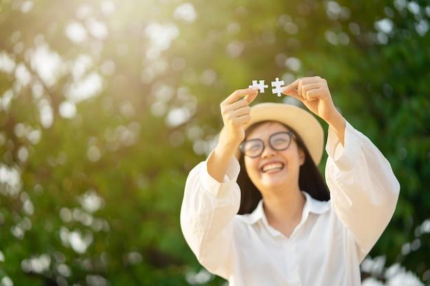 2つのジグソーパズルを示す幸せな女の子。愛の完了。