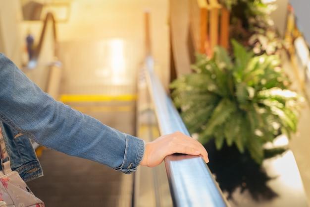 モールの2階にあるエスカレーターに乗る女性の視点。エスカレーターレールを保持しているフレームに片手が見える。