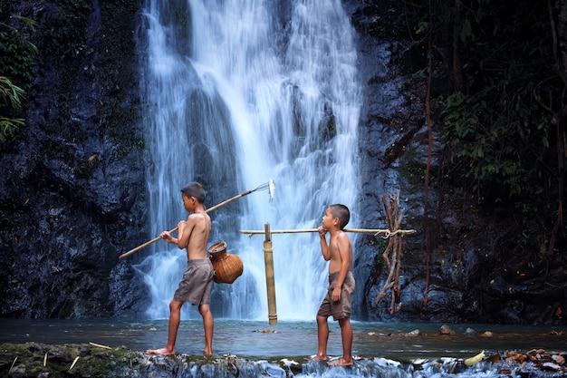 2人の男の子が遊んで笑う滝で釣り