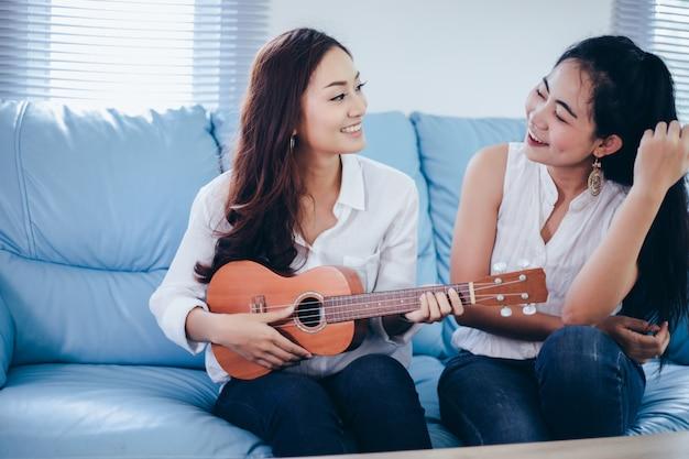 2人のアジアの女性が楽しくウクレレを弾き、リラックスタイムのために自宅で笑顔を浮かべています