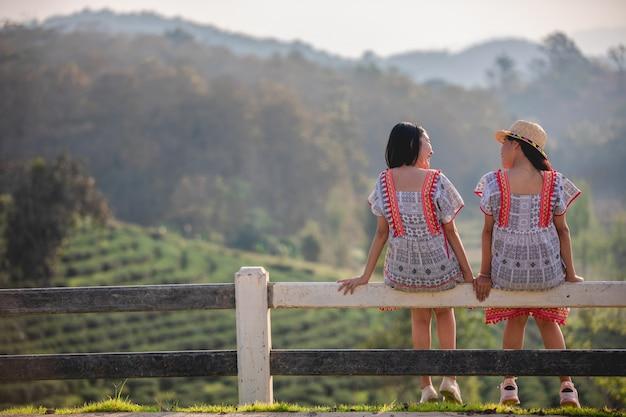 日没の庭のフェンスの上に座っている2人のアジアのかわいい、若い女の子