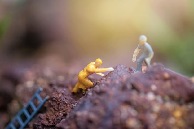 山の頂上に到達するために互いに助け合っている2人の友人のミニチュア