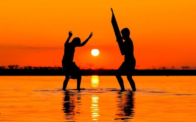 Мальчик 2 играя может, музыкальные стили северо-восточный таиланд в озере на предпосылке захода солнца.