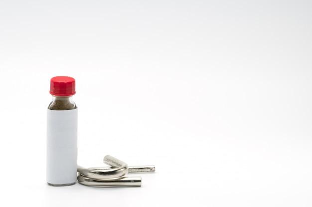 赤いキャップとスチールとクロムで作られた2つの嗅ぎ管付きの古典的なボトルのタイのハーブパウダー嗅ぎタバコ