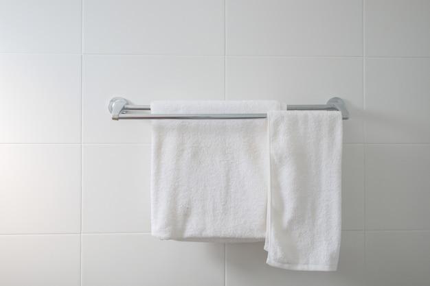 白いタイル壁のスチールレールに掛かっている2つの白い乾いたタオルで空のバスルームをクローズアップ