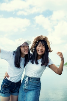 海のビーチで2つの陽気なアジアのティーンエイジャー幸福感情