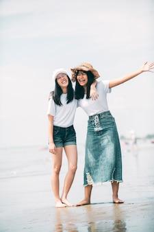 休暇海ビーチに2つの陽気なアジアのティーンエイジャー幸福