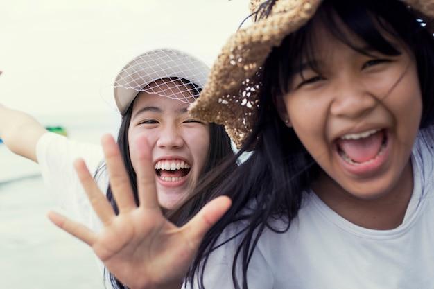 2つのアジアのティーンエイジャー幸福感情の歯を見せる笑顔