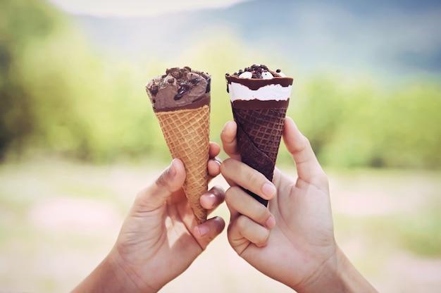 自然の背景でアイスクリームコーンを保持している2つの手