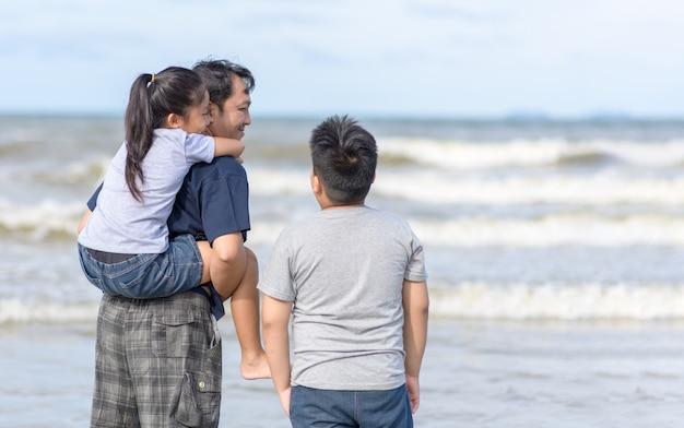 父とビーチの上を歩く2人の子供
