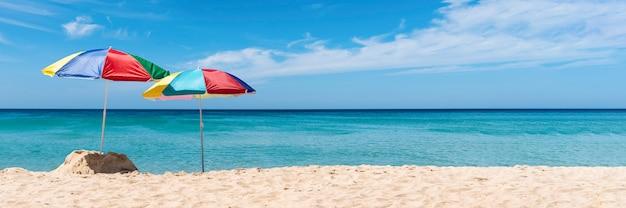 熱帯のビーチに2つの傘。夏の休日バナー