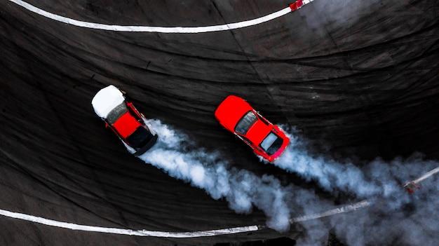 車のドリフトバトル、煙が付いているレーストラック上の2台の車の漂流バトル、空撮。